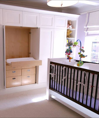 Doors in a built in closet in a New York nursery open to reveal a changing table by  Area Interior Design
