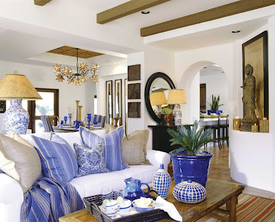 White open plan living room by Barclay Butera with blue accents in the form of pillows, vases and pottery