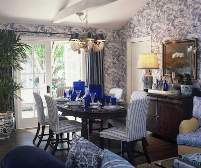 Traditional dining room with blue tolie wallpaper, upholstered blue and white striped dining chairs, Asian inspired blue and white ceramic lamp and garden stool by Barclay Butera