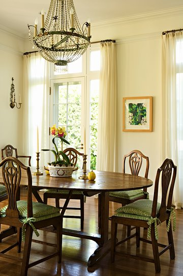Traditional dining room with a large crystal chandelier, dark stained wood table, Queen Anne chairs with green cushions and off white walls