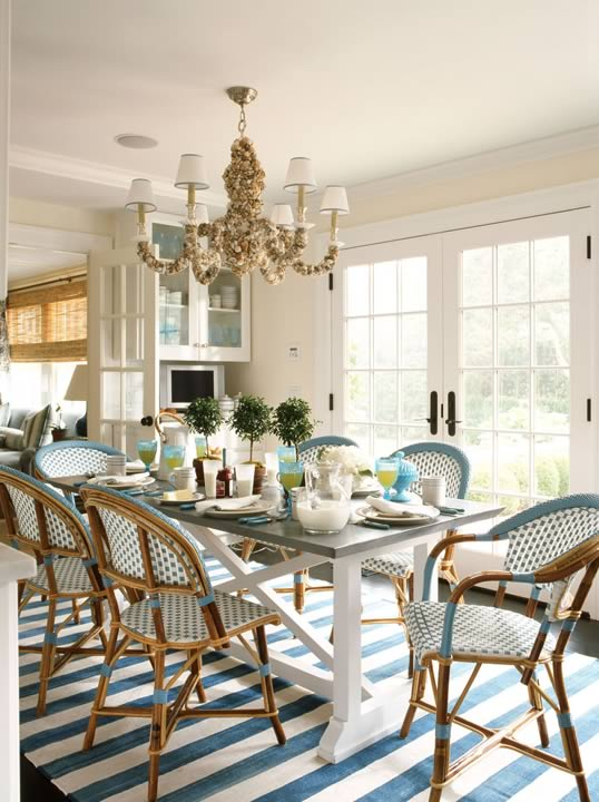 South Hamptons beach house dining space with classic French blue and white bistro chairs, a long farmhouse table with a white X-base and a grey top, a sea shell chandelier and a blue and white striped rug