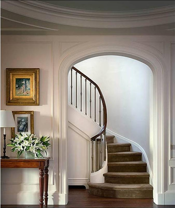 Archway leading to a curved staircase in a New York apartment by Katie Leede