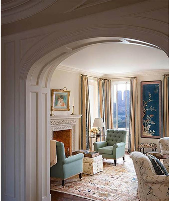 Living room designed by Katie Leede with arched doorway, light teal tufted velvet upholstered armchairs, off white with blue floral seating, striped curtains and a view of New York City
