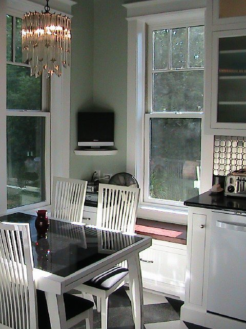 Kitchen after remodeling with a breakfast nook with a white table with a black insert