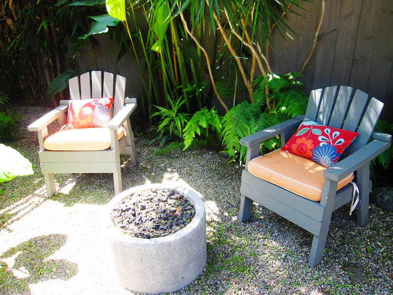 Outdoor chairs with bright accent pillows around a fire pit in a backyard in Venice Beach, CA