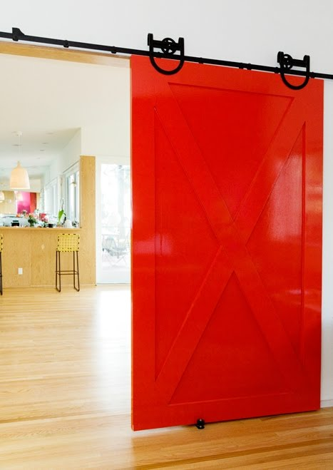 Red interior barn door slides on black metal exposed hardware leading to a kitchen by Bestor Architecture