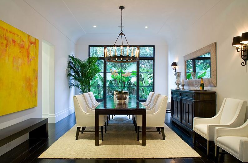 Formal living room in a Spanish revival home with white armchairs around a long dark wood table and a jute rug