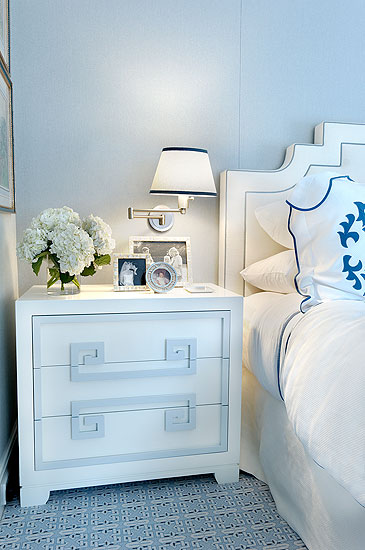White nightstand in a master bedroom with white headboard and blue graphic print carpet
