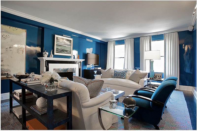Blue living room with Madeline Weinrib ikat pillows, a tight back tufted white sofas, and a mirrored fireplace surround