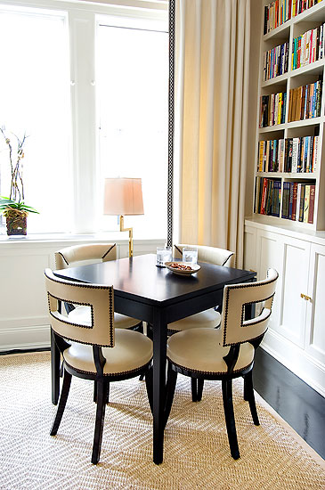 Side table in a living room surrounded by dark wood chairs with white leather seats and back with nail head trim, floor length curtains and a white built in bookshelf
