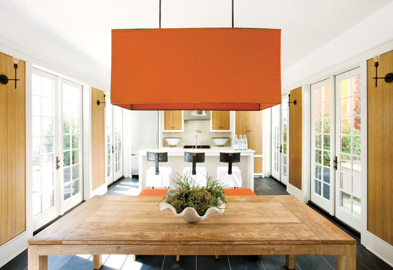 Kitchen in a Florida beach home with a large orange pendant light, orange stools, zebra wood cabinets, french doors and dark slate floor