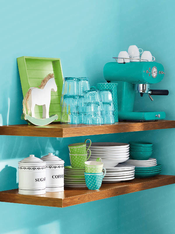 Floating shelves in a small turquoise kitchen with matching accessories