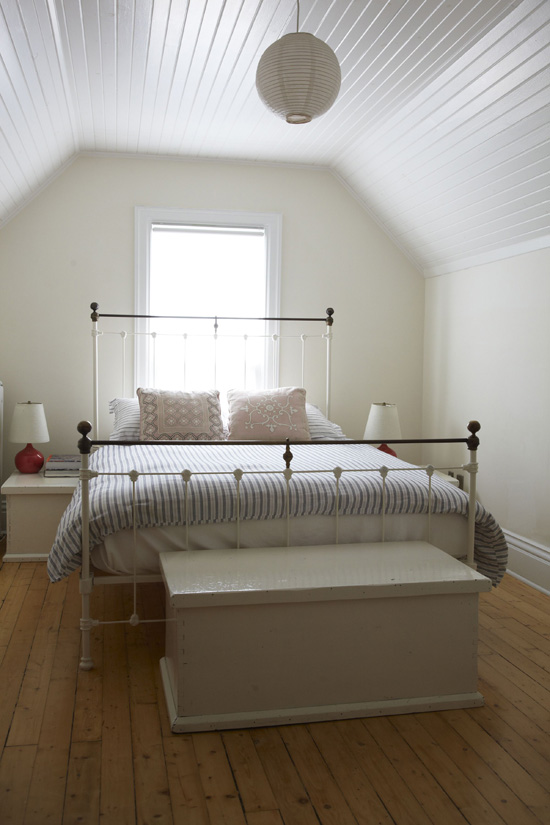 white bedroom with white beadboard ceiling wide plank wood floor
