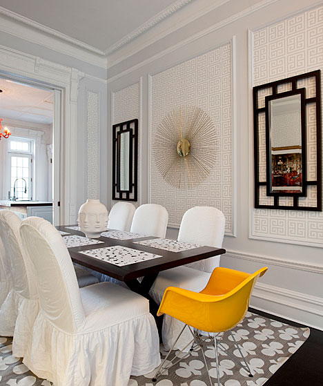 Dining room with decorative mirrors, Greek key wallpaper, slipcovered chairs and a bright yellow Eames chair