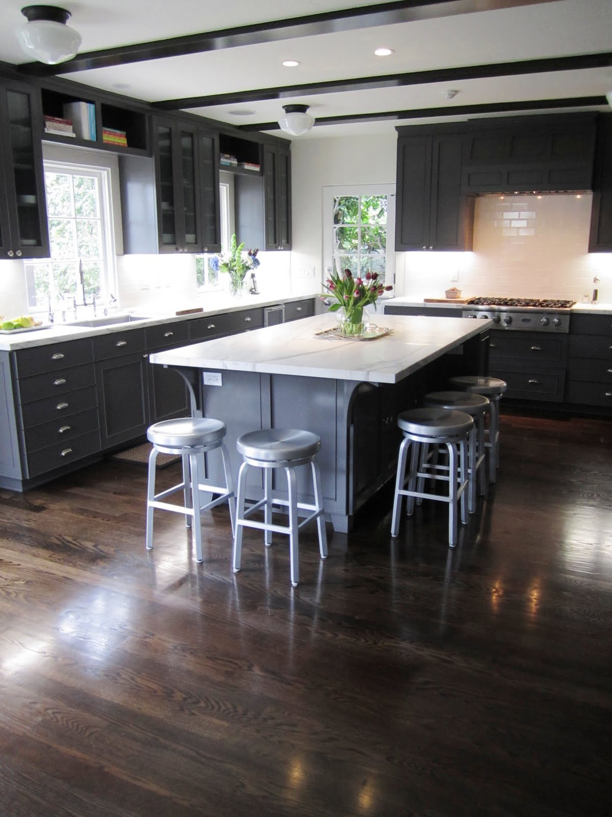 kitchen with dark grey cabinets and drawers school house lighting and dark stained wood beams