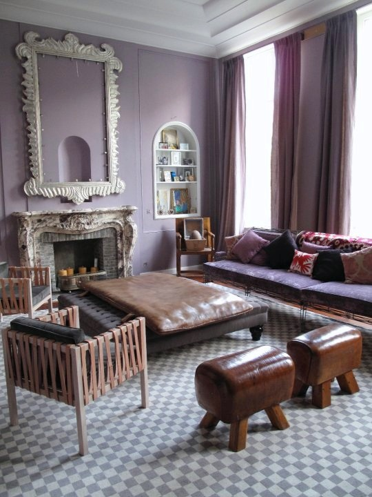 Purple living room in a Brussels apartment with lavender walls, grey and white checkerboard floor, antique fireplace with a large white mirror on the mantel, tufted black ottoman, to leather stools, armchairs with leather straps and a purple sofa with exposed metal legs