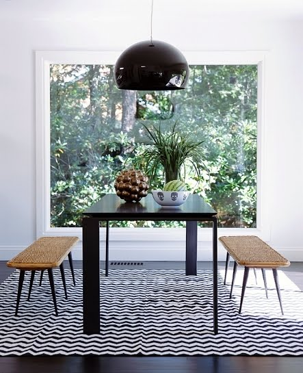 Dining room with benches, dark table with mismatched legs, black and white chevron rug, a large picture window and a black dome style pendant light