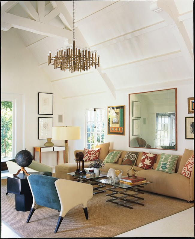 Living room with exposed beams and pointed ceiling, two toned 1960s Gio Ponti chairs, a gold chandelier, sisal rug and tan sofa with bright accent pillows, a large mirror and glass coffee table with metal base
