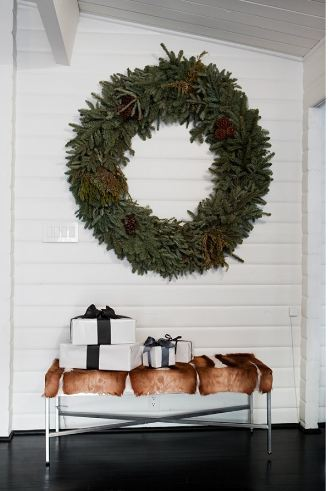 Foyer with dark wood floor, beadboard wall, a bench holding four presents and a large wreath