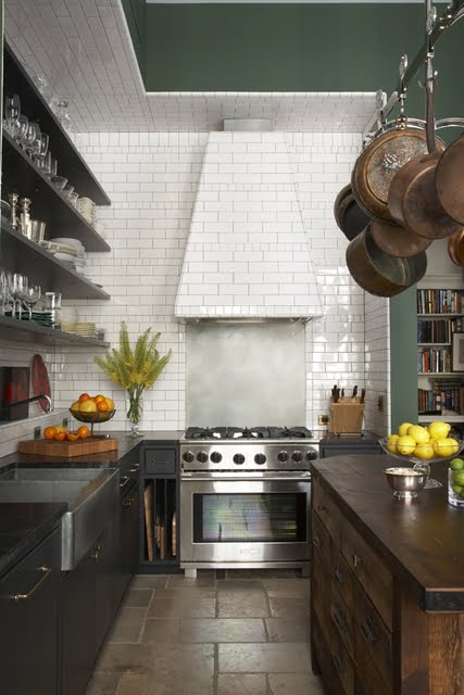 Kitchen with dark wood cabinets, floating shelves, subway tile backsplash, stainless appliances, a hanging pot rack and an island with stained wood cabinets and a wooden counter top