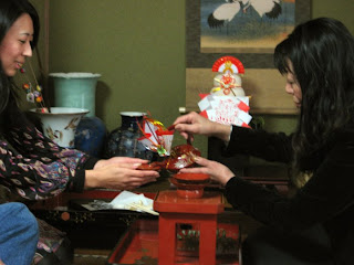 Morinaga-san pours sacred sake for her daughter in a New Year ritual -- note the decorations behind them as offerings to the gods, and the scroll on the wall with cranes to represent happiness.