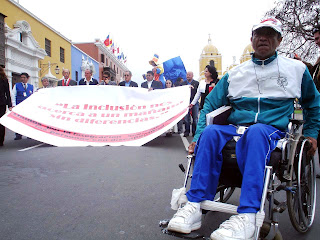 Imagen de personas con discapacidad manifestándose con una pancarta en la que pone la inclusión nos acerca a un mañana sin diferencias