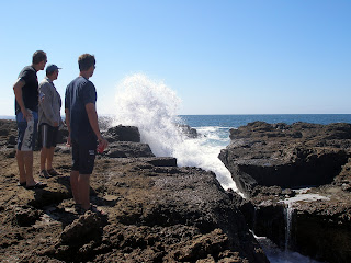 Watching the waves crash through the volcanic reef