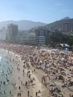 Crowded Ipanema Beach with the Christ the Redeemer statue in the distance.