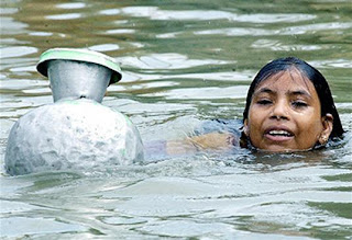 A girl swims through floodwaters with an empty vessel to collect drinking water in Dhaka's low-lying area. Photo: Shawkat Khan