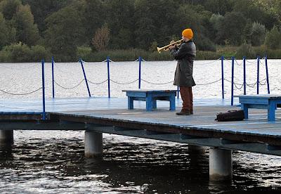 Facet grający na trąbce nad jeziorem