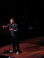 Luz focal sobre Alejandro Sanz no palco cantando com piano ao fundo