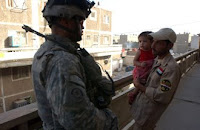 Staff Sgt. Koke Pomele, an infantry squad leader attached to the 1st BCT, 4th ID, MND-Baghdad, answers questions of a resident Son of Iraq (Abna al-Iraq) during cordon and search operations around the Saha apartments in the southeastern Rashid District of Baghdad. Photo by Staff Sgt. Brent Williams.