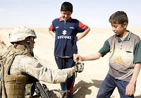 Lance Cpl. Israel H. Aguirre pounds fists with an Iraqi child near Hit, Iraq. (Marine Corps photo by Cpl. Seth Maggard)