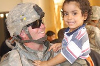 Staff Sgt. Joseph Reinsburrow holds an Iraqi child June 12 in Hurriyah, while Iraqi Police and Coalition forces hand out toys and school supplies to the local children. (Army photo by Sgt. Daniel Blottenberger)