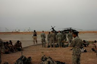 Soldiers with Grim Troop, 2nd Squardon, 3d Armored Cavalry Regiment and the 5th Iraqi Army Division sit on the helipad at Forward Operating Base Caldwell waiting to begin an air assault mission, July 25, 2008. The Soldiers will be inserted into the dangerous village of al Fatah Miaya to drive out the insurgents. ID: 106500; Date Taken: July 31st, 2008; Location: Tikrit, IQ; Photographer: Sgt. Kyle Richardson, 11th Public Affairs Detachment