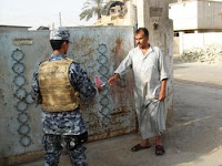 A resident of the Aamel neighborhood receives a wanted poster handbill from an Iraqi national policeman Sept. 11, 2008, in the Rashid district of southern Baghdad. The wanted poster offers rewards of up to $50,000 for the capture of these special groups criminals and militia leaders expected to return to the area.