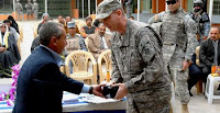 Muzhir Ali Salman, General Cooperative Union chairman, presents a souvenir to Army Col. Ted Martin during the Saydiyah Fish Market's ribbon-cutting ceremony in southern Baghdad, Feb. 9.