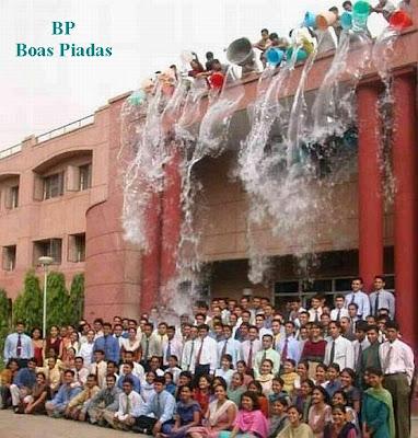 Grupo de pessoas se prepara para posar para uma fotografia de formatura  enquanto outros, de cima do prédio estão prontos para jogar-lhes água.