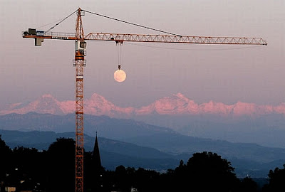 Paisagem em que a lua aparenta estar sendo carregado por um guindaste.