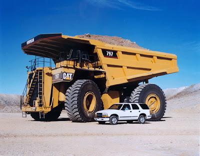 Caminhão para mineração ao lado de um carro de passeio comum.