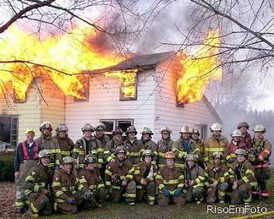Bombeiros posam para fotografia em frente a uma casa que arde nas chamas de um incêndio.