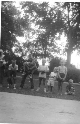 Children of the Sylwester and Hackmann families posing in a line in a yard on Faculty Lane in Seward, Nebraska. The image was scanned from a photograph belonging to Toby Beck.