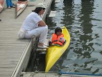 Fotografia da Carla Ferreira no kayak, encostada ao cais, com uma amiga na margem