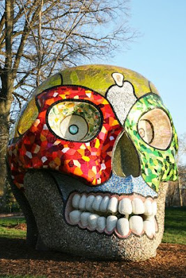 This six-ton smiling skull was inspired by a trip Niki made to Mexico in the late 1970s. She liked the cheerful way in which Mexicans deal with the subject of death. -- The Mexican tradition of the Day of the Dead seems to inform La Cabeza as a face of death that is both festive and contemplative. It pulls viewers in as it reflects life back. -- The piece is an inventory of the materials Niki used, from mother of pearl, to geometric mirrored glass, to the translucent round glass pieces that she called M&M's. This skull is fully interactive and easily accessible. -- Go inside to look around or have a seat in its domed meditation room, with its blue sky and moon.