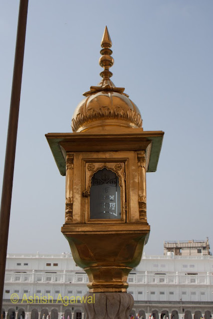 Gold plated lamp posts at the edge of the causeway inside the Golden Temple in Amritsar