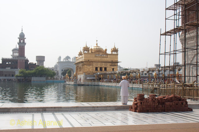 Devotee standing at the edge of the tank, paying respect to the Darbar Sahib inside the Golden Temple