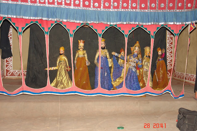 Photo of the various puppets against the background of a curtain at Chokhi Dhani