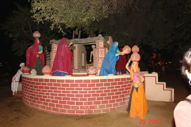 Various village people around a well, carrying pots in the village of Chokhi Dhani