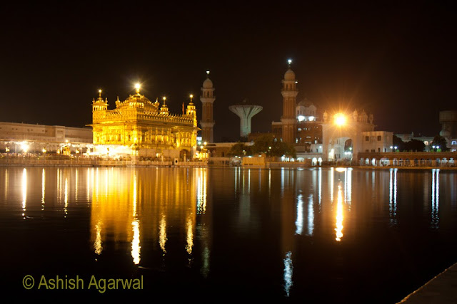 A more distant view of the beautifully lighted Golden Temple at the far end of the sarovar in Amritsar
