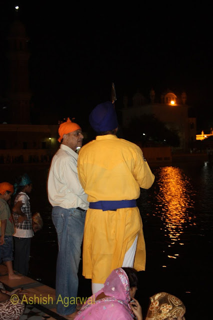 Devotees and a volunteer at the Golden Temple in Amritsar at night